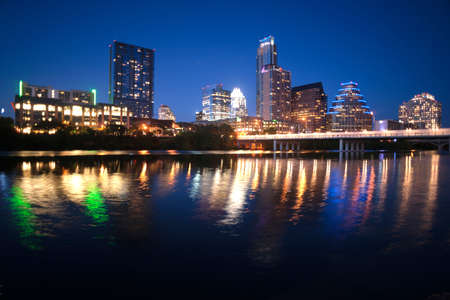 As the sky darkens the city lights brighten and get reflected in the Colorado River Stock Photo