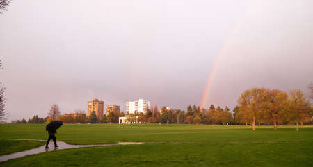 denver city park: The sun peaks through for a moment lighting the way and producing a rainbow near a person walking with umbrella Stock Photo