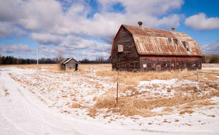 old barn in winter: Fresh snow sits on the ground around an old barn
