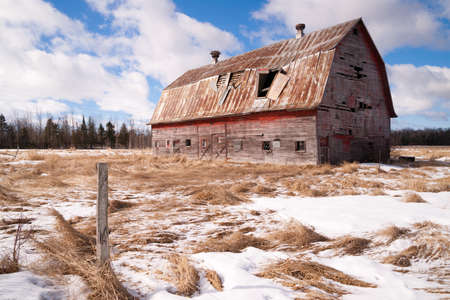Fresh snow sits on the ground around an old barn photo