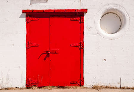 stark: Stark composition contrast between red door and white walls at lighthouse base Stock Photo