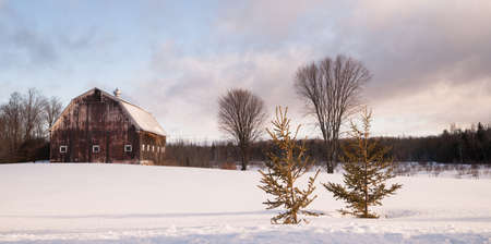 Fresh snow sits on the ground around an old barn