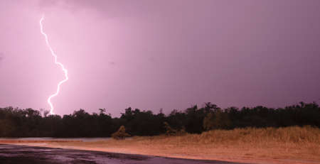 inclement: Lightning Strikes over a river in southeast Texas Stock Photo