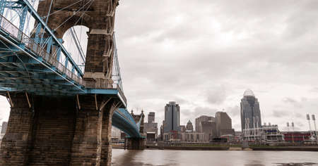 urban sprawl: The Ohio River is at flood stage as it passes underneath a historical suspension bridge