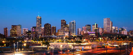 denver skyline with mountains: The buildings and architecture of Denver Colorado at dusk