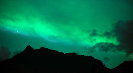 aurora borealis: The Northern Lights emerge through the clouds in remote Alaska