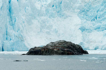 calving: A large rock outcropping sits in front of a calving glacier Stock Photo