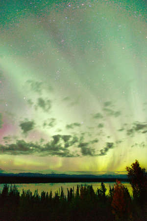 emerge: The Northern Lights emerge through the clouds in remote Alaska