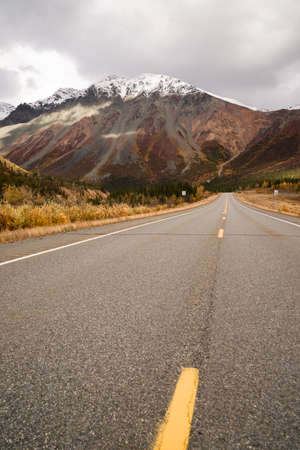 autumn road: The sun peeps through a partly cloudy sky to light the Alaska Range