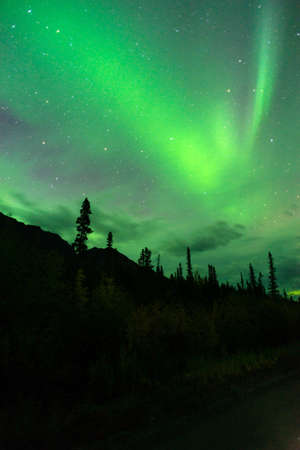 ionosphere: The Northern Lights emerge through the clouds in remote Alaska