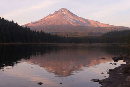 Mount Hood stands alone in the fall at sunrise ubove peaceful Trillium Lake
