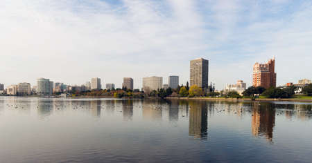 An overcast sky is reflected in the smooth water of Lake Merritt in front of Oakland