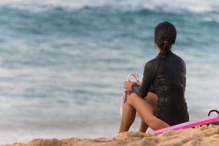 waits: A fit and trim woman waits for the right conditions to enter the water out on the beach Stock Photo