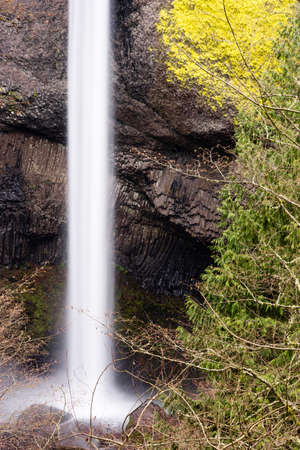 cliff face: A solid beam flow of water from Mt Hood rushes down the cliff face