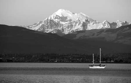 mt baker: A boat travels the water at sunset in Puget Sound Washington Stock Photo