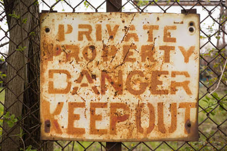 out of danger: Private Property Danger Keep Out Sign Rusted Fence Stock Photo