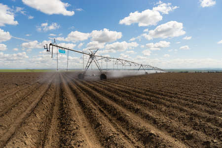 A watering sytem moves along on top of the freshly plowed field Stock Photo