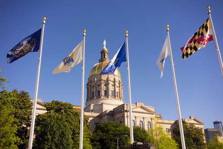 The golden capital dome stands out against a blue sky in Atlanta flags waving Stock Photo