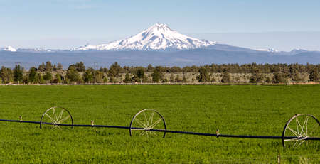 Farm irrigation tools stand in the farm fields near Mt Jefferson on Warm Springs Reservation Stock Photo
