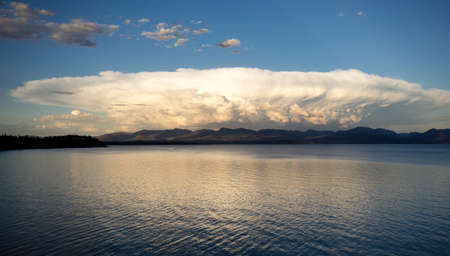mushrooming: This monster mushrooming cloud billows with light at sunset over Yellowstone Lake Stock Photo