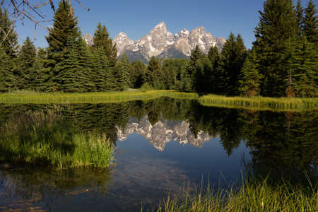 The water is perfectly smooth showing high peak reflections in the Tetons Stock Photo