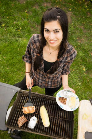 backyard woman: Pretty Woman Smiling Cooking Steaks Barbecue Backyard Food Grill Stock Photo