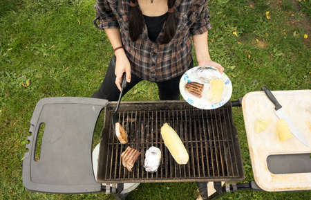 cook out: Female plates up the food at the backyard cook out