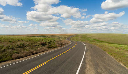 A central Washington State road winds out into the distance below fluffy blue clouds