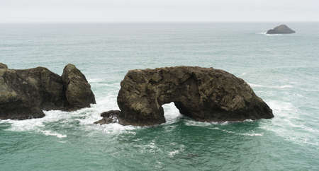 Surf crashes up against Arch Rock off the Oregon Coast Stock Photo