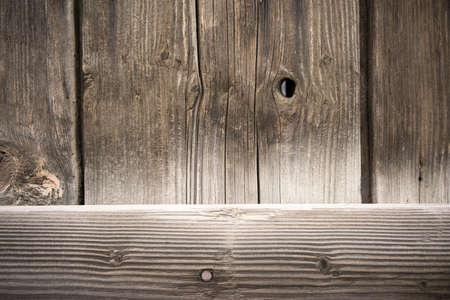 Looking thru a crack in the wood plank barn wall with a big knot