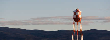water tower: A utility water tower stands brightly at sunset Stock Photo