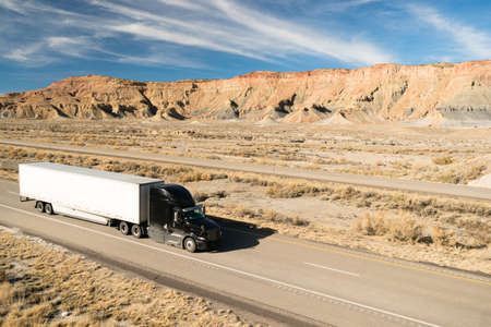 A black big rig rolls across Utah on a devided highway Stock Photo