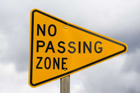 a reflective sign bolted to a post says no passing zone Foto de archivo