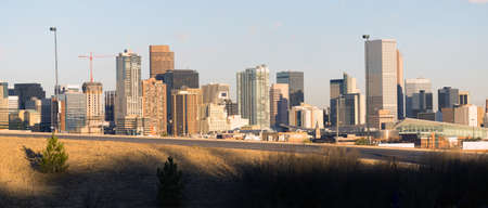 A view of Denver behind a highway onramp at sunset Stock Photo