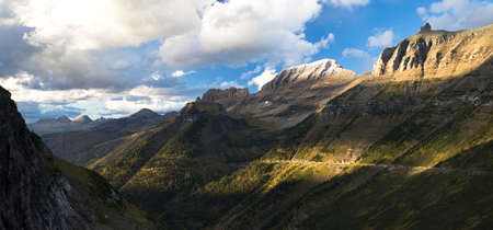 High peaks of the rocky mountains loom over the highway in Glacier National Park Stock Photo