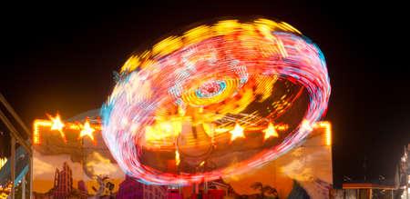 Las luces que circulan en un paseo de carnaval crean rayas rojas Foto de archivo
