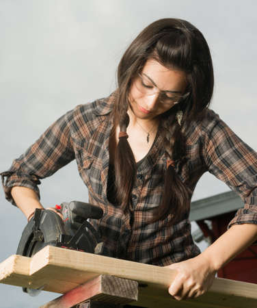 Brunette woman in pigtails cuts 2x4 boards with battery operated saw Stock Photo