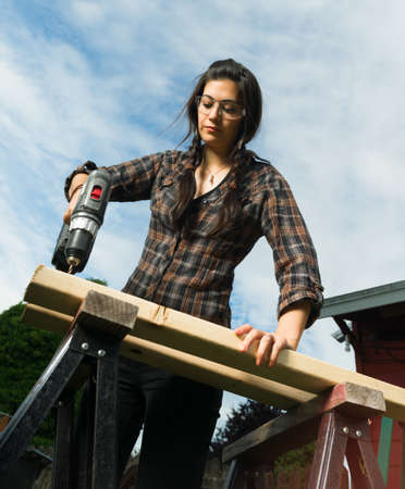 Brunette woman in pigtails drilling 2x4 boards with battery operated drill Stock Photo