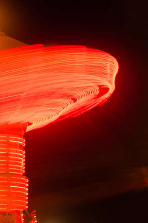 county fair: Lights going around on a carnival ride create red streaks