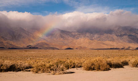 Clouds hug the Sieera Nevada Range tight as a rainbow forms in the mist