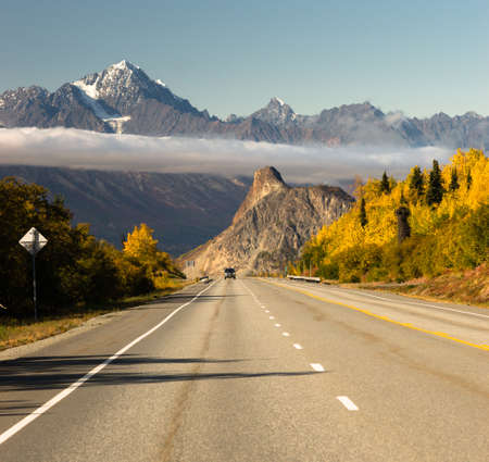 A vehicle drives toward the camera below the Chugach Mountains in Alaska