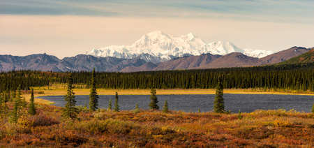 The sun finally rises but stays low in the sky hitting Mount McKinley and the Denali range on a long summer day in Alaska