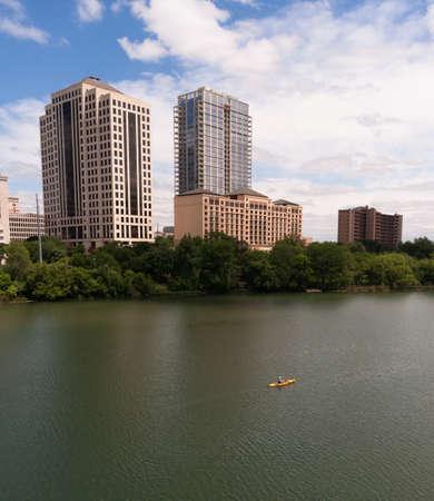 A Kayaker moves along the Colorado River dwarfed by the Austin Skyline Stock Photo