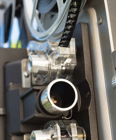 A large film reall is mounted on a vintage Super 8 movie projector Stock Photo