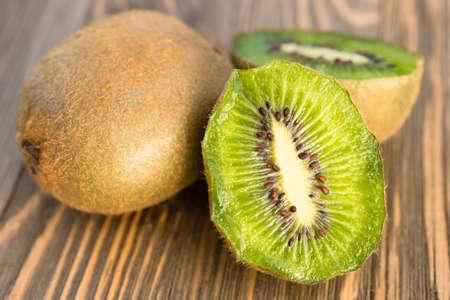 Two Kiwi Fruits sit on the cutting board on cut in half Stock Photo