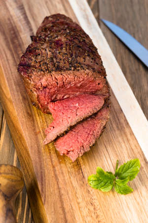 A large piece of grilled top sirloin sits on cutting board sliced and peppered