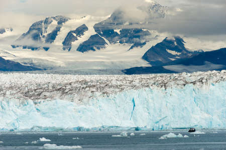A small bought tries to navigate the icebergs in Kenai Fjords
