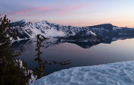 Sunrise generates pink hues over Crater Lake National Park