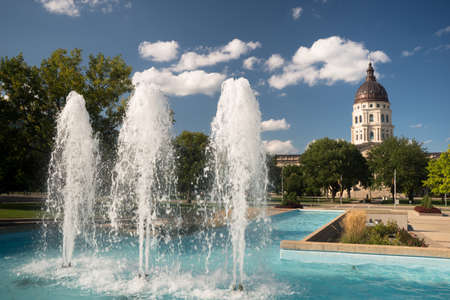 Soft clouds and blue skies appear over fountains and the capitol of Topeka, Kansas USA Фото со стока