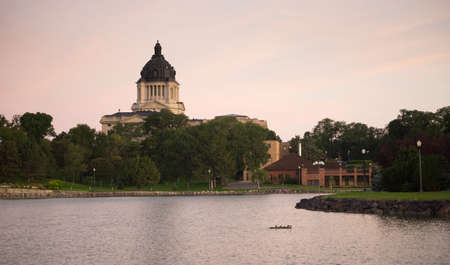 Water from the lake reflects the building in front of the capitol dome in Pierre, SD